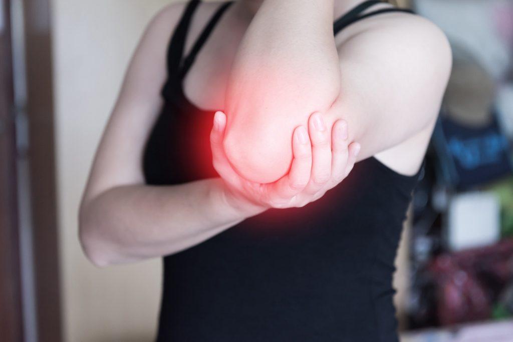 Frau mit chronischen Schmerzen hält sich den Arm fest